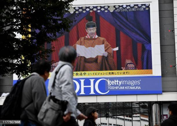 People look at a screen displaying Japan's Emperor Naruhito attending the enthronement ceremony where he officially proclaims his ascension to the...