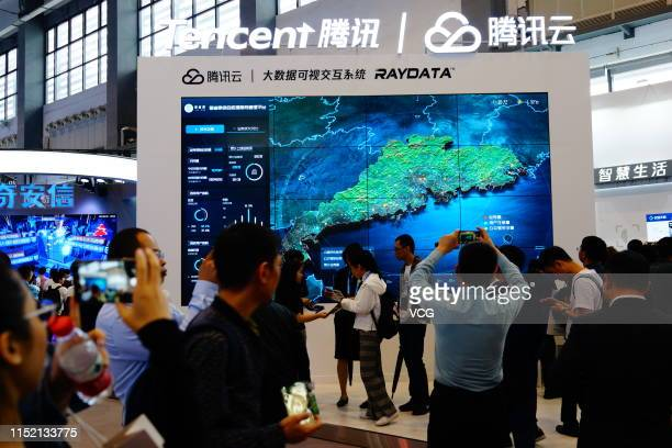 People look at a screen featuring big data visual interactive system at the Tencent stand on the opening day of China International Big Data Industry...