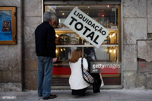 People look at a shopfront in central Lisbon with a sign saying 'Total sellout' in Lisbon on December 16 2013 after the results of the tenth of...