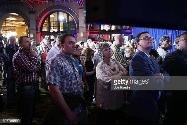 People look at a television news broadcast showing Republican presidential candidate Donald Tump is leading the election vote tally against...