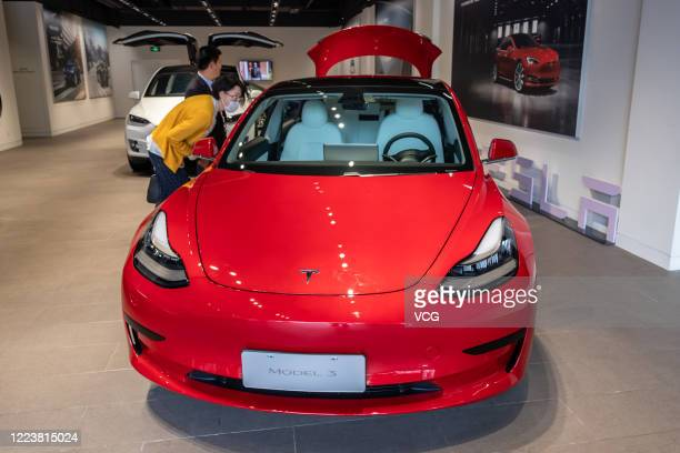 People look at a Tesla Model 3 car at the first Tesla Center in Shanghai on May 9 2020 in Shanghai China