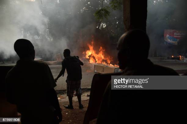 People look at a truck carrying refigerators that was set on fire by demonstrators during a protest against the remobilisation of the army and angry...
