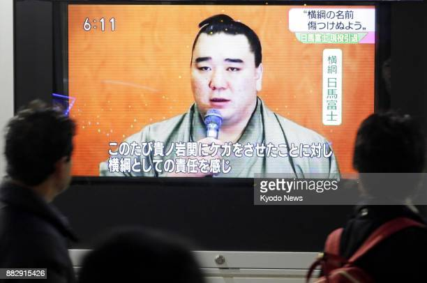People look at a TV screen in Tokyo on Nov 29 reporting sumo grand champion Harumafuji's retirement over an assault in late October on fellow...