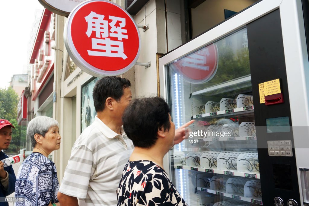 People Look At A Vending Machine Dispensing Hairy Crabs In