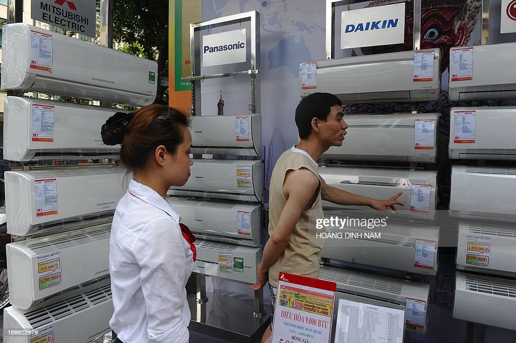 People look at air conditionners displayed for sale in front at an electrical store in downtown Hanoi on May 17, 2013. The demand for air conditioners rose up since the country is facing the first severe heat wave at the beginning of this summer which is expected to be hard this year according to weather forecast reports. AFP PHOTO/HOANG DINH Nam
