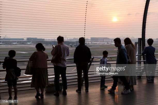 People look at aircraft at Haneda Airport at dusk ahead of Golden Week on April 21 2019 in Tokyo Japan Japanese people will enjoy a rare 10...