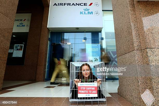 """People look at an activist of the People for Ethical Treatment of Animals imprisoned in tiny cage with a banner reading: """"Air France, Stop Shipping..."""