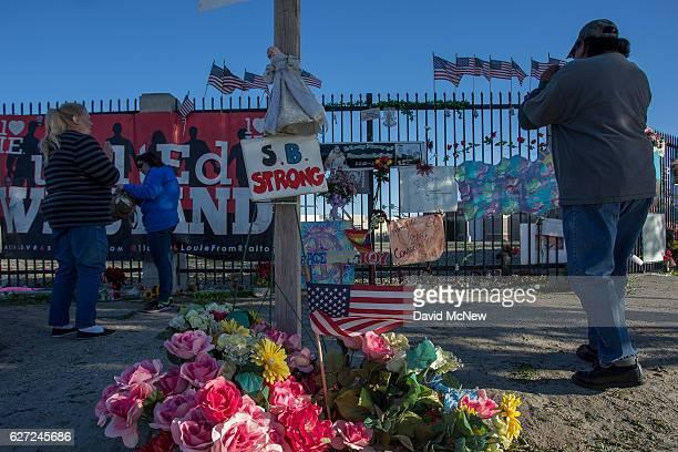 People look at an aging makeshift memorial on one-year anniversary of the San Bernardino massacre on December 2, 2016 in San Bernardino, California....