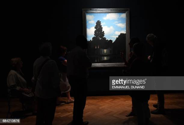 People look at an artwork by Belgian surrealist artist Rene Magritte at the Magritte Museum in Brussels on May 17 ahead of a series of exhibitions...