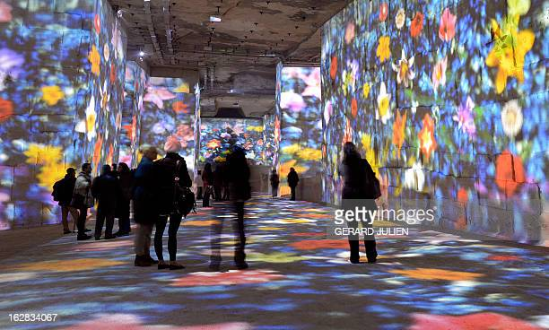 People look at an audio visual show projected on the walls of the 'Carrieres de Lumieres' site 'Rêve' on February 28 in the southern French city of...