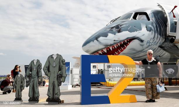 People look at an Embraer E190E2 aircraft displayed at the Farnborough Airshow south west of London on July 19 2018