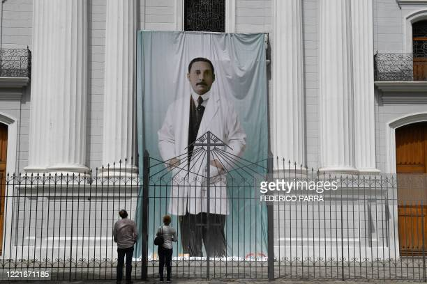 People look at an image of Venezuelan doctor Jose Gregorio Hernandez outside La Candelaria church which holds his remains in Caracas on June 21 2020...