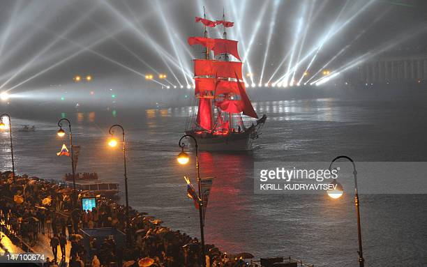 People look at an oldfashioned tall ship on the Neva River in St Petersburg early on June 24 during the 'Scarlet Sails' a romantic holiday with laser...