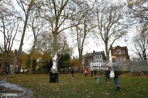 People look at and photograph a new sculpture honouring 18th century British author and feminist icon Mary Wollstonecraft by British artist Maggi...