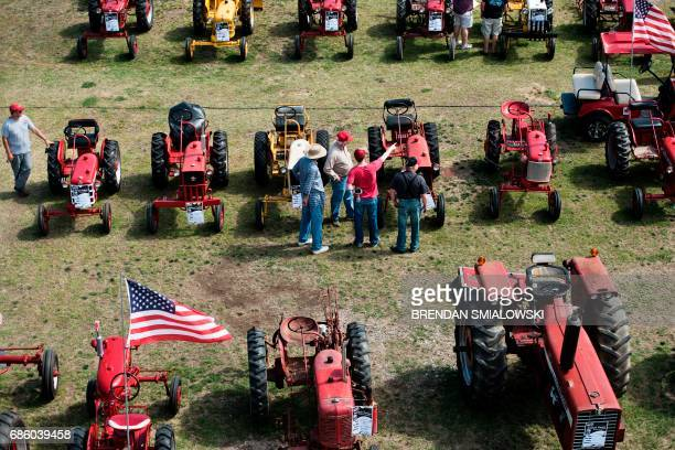 People look at antique tractors during the Got to Be NC Festival on the North Carolina State Fairgrounds May 20 2017 in Raleigh North Carolina / AFP...