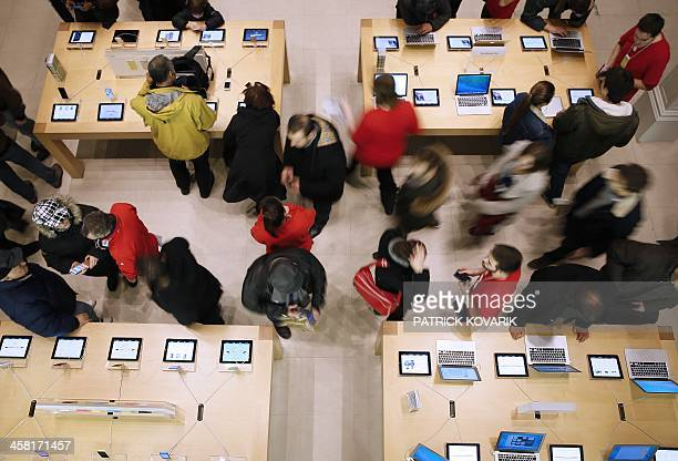 People look at Apple products at one of the company's stores in Paris on December 20 2013 AFP PHOTO / PATRICK KOVARIK