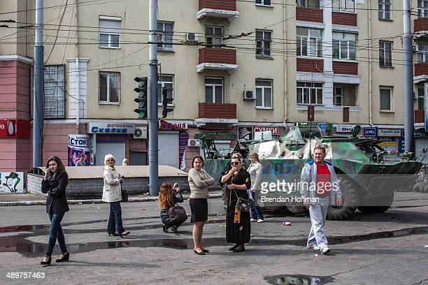 People look at at an armored personnel carrier parked in the middle of the city after it was commandeered by proRussia activists on May 12 2014 in...