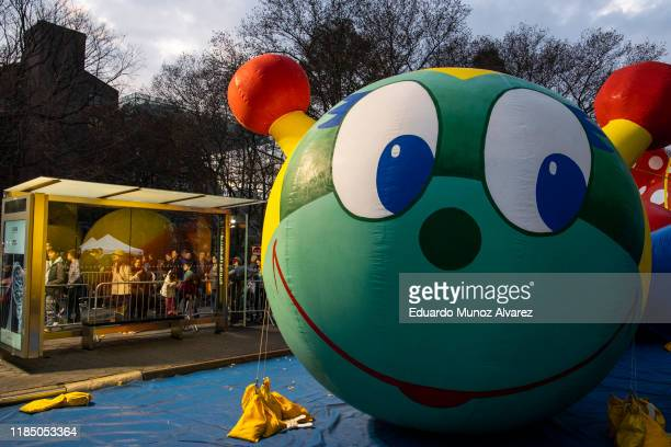 People look at balloons during the inflation process on November 27 2019 in New York City Winds could ground the giant balloons according to city...