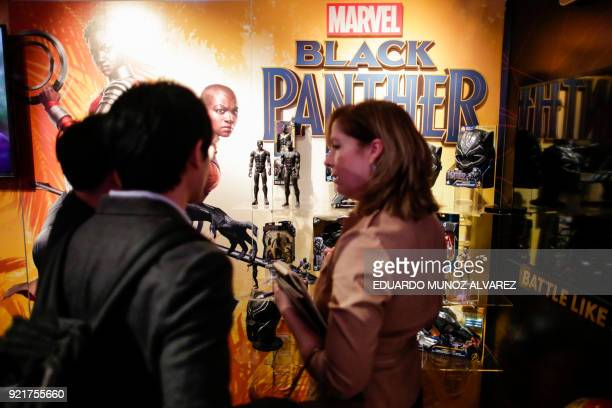 People look at 'Black Panther' items at the Hasbro showroom during the annual New York Toy Fair on February 20 in New York Panther claws masks and...