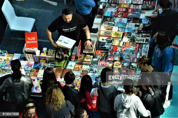 People look at books in front of a stand during the 12th International Ankara Book Fair in Ankara Turkey on February 17 2018