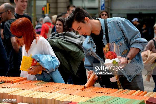 People look at books on the Ramblas boulevard during Sant Jordi festivities in Barcelona on April 23 on Saint George's day. - Traditionally men give...