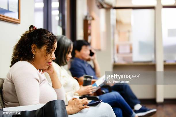 people look at brochure and use smart phones while waiting - waiting stock pictures, royalty-free photos & images