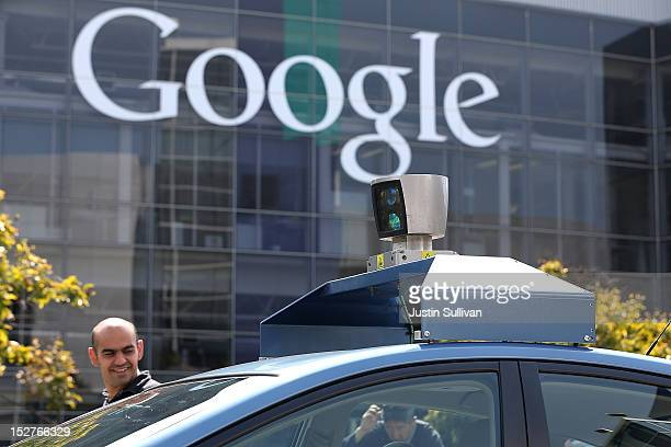 People look at camera on top of a Google selfdriving car at the Google headquarters on September 25 2012 in Mountain View California California Gov...