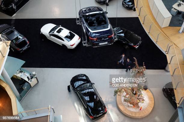 People look at cars of German automobile brand MercedesBenz on display at a Mercedes car dealership in Berlin on March 25 while a model of an EClass...