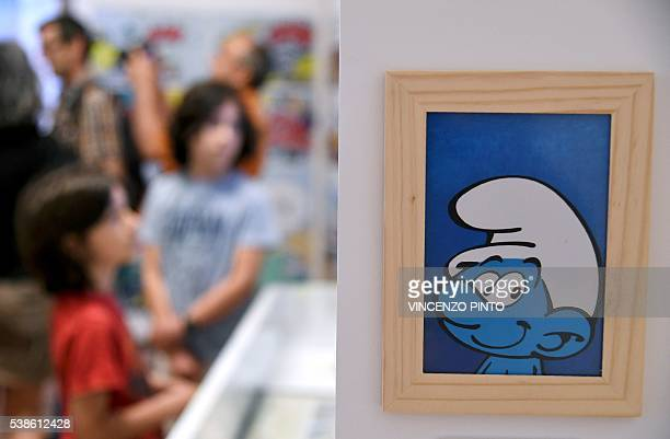 People look at cartoons boards of the Smurfs created by the Belgian cartoonist Pierre Culliford who worked under the pseudonym of Peyo during the...