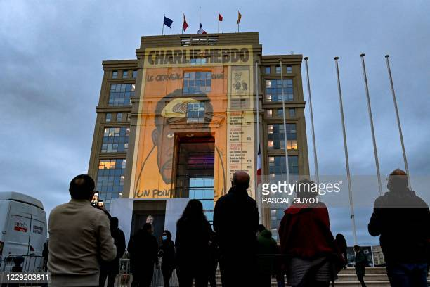 People look at cartoons of French satirical weekly newspaper Charlie Hebdo projected onto the facade of the Hotel de Region in Montpellier, on...