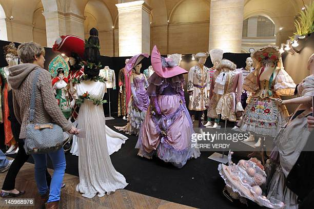 People look at costumes from the Folies Bergere displayed at the Palais de la Bourse as part of the Ventes de folie auction in Paris on June 8 2012...