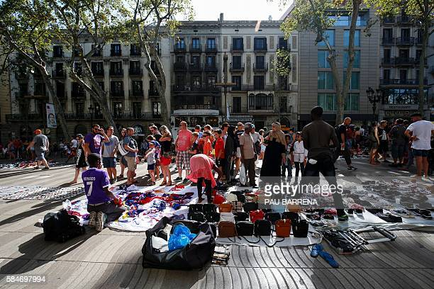 People look at counterfeit tshirts goods displayed on vendors blankets in the illegal street market near Canaletas source in Barcelona on July 30...