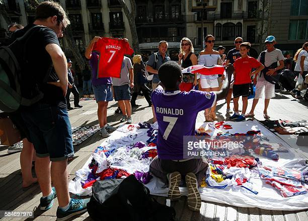 People look at counterfeit tshirts of football players displayed on a vendors blanket in the illegal street market near Canaletas source in Barcelona...