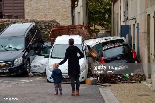 TOPSHOT People look at damaged cars following heavy rains that saw rivers bursting banks on October 15 2018 in Villegailhenc near Carcassonne...