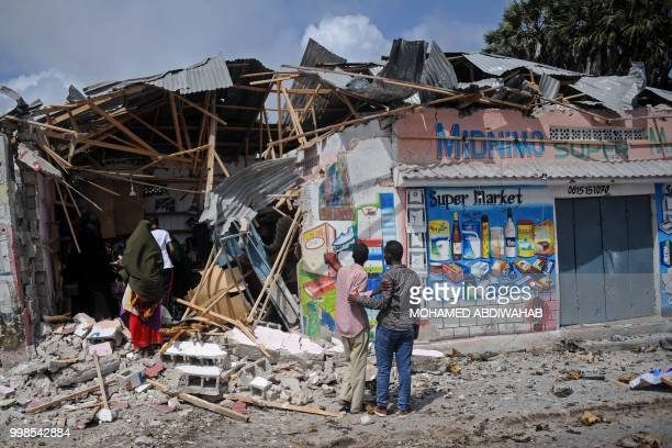 People look at damaged shops after two car bombs were detonated and three Shabaab gunmen were shot dead after exchanging fire with security forces...