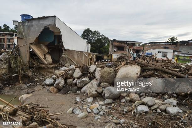 TOPSHOT People look at damages caused by mudslides following heavy rains in Mocoa Putumayo department southern Colombia on April 2 2017 The death...