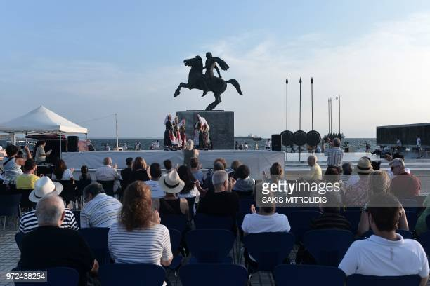 People look at dancers wearing traditional costumes performing in front of the statue of Alexander III of Macedon commonly known as Alexander the...