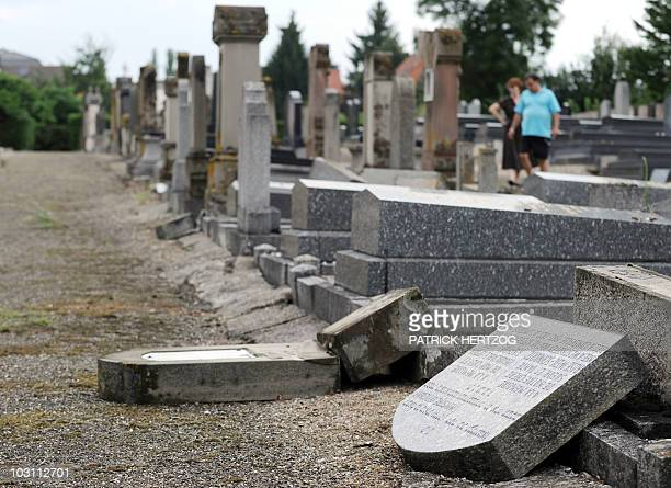 People look at desacrated graves at the jewish cemetery of Wolfisheim, near Strasbourg, eastern France, on July 21, 2010. 27 graves were desacrated...