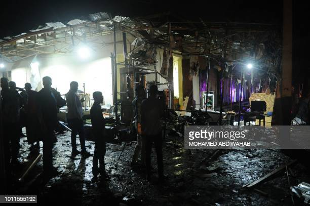 TOPSHOT People look at destruction at the site of a car bomb explosion in Mogadishu on August5 2018 At least three were killed and five others...