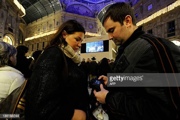 People look at Don Giovanni, the opera opening the 2011-2012 season of La Scala opera house, broadcasted live in the Vittorio Emanuele II gallery...