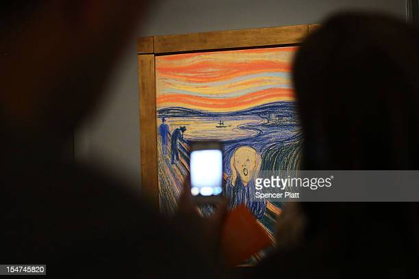 """People look at Edvard Munch's """"The Scream,"""" which went on display in Manhattan's Museum of Modern Art for a six-month exhibition October 25, 2012 in..."""