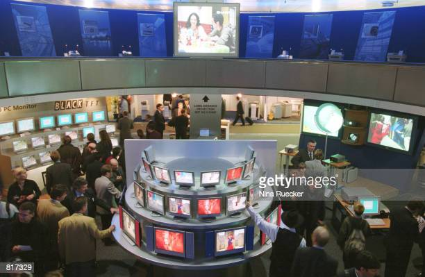 People look at exhibits at CeBIT, the world's largest consumer trade show, March 24, 2001 in Hannover, Germany. More than 8,000 companies will...