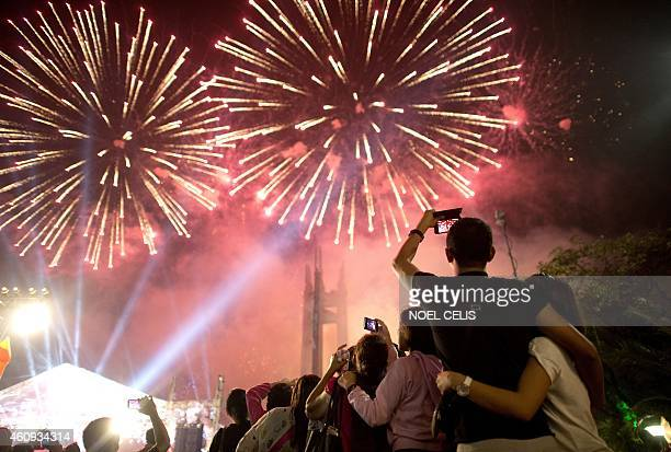 People look at fireworks during a New Year Celebration in Manila on January 1 2015 The Philippines is mainly Roman Catholic but the celebrations draw...