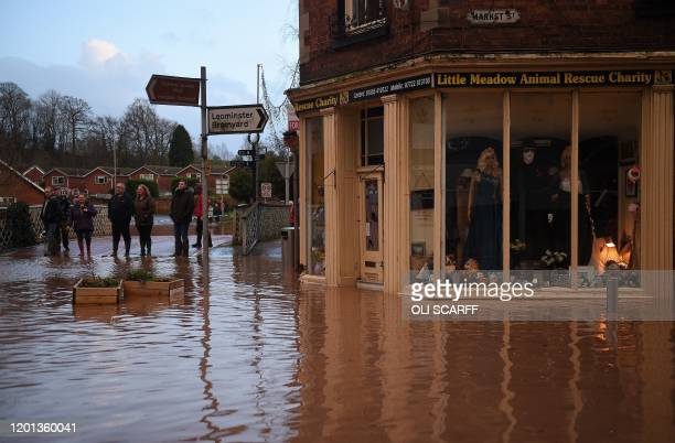 TOPSHOT People look at flood water in Market Street in Tenbury Wells after the River Teme burst its banks in western England on February 16 after...