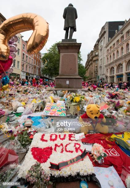 People look at flowers in St Ann's Square in Manchester northwest England on May 29 placed in tribute to the victims of the May 22 terror attack at...