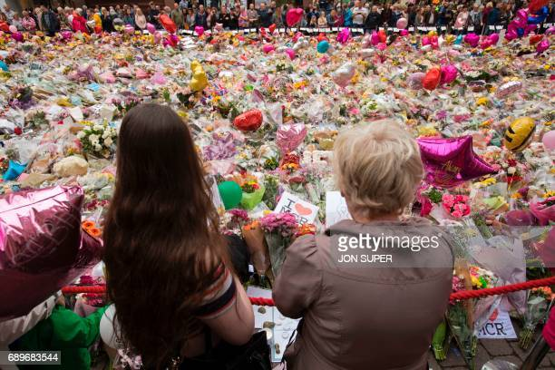 TOPSHOT People look at flowers in St Ann's Square in Manchester northwest England on May 29 placed in tribute to the victims of the May 22 terror...