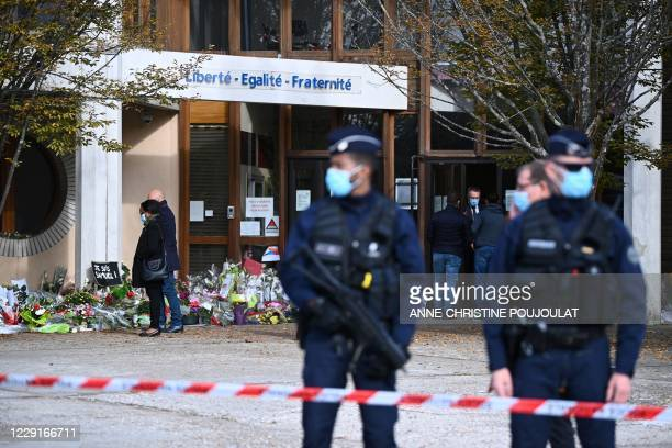 People look at flowers layed outside the Bois d'Aulne secondary school in homage to slain history teacher Samuel Paty, who was beheaded by an...