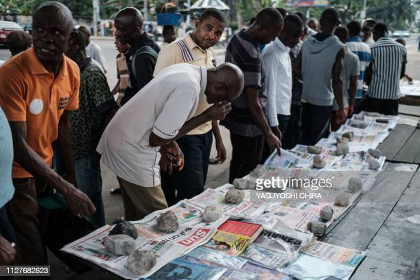People look at frontpages after Nigeria's Presidential election results at a newspaper stand in Port Harcourt Southern Nigeria on February 27 2019...