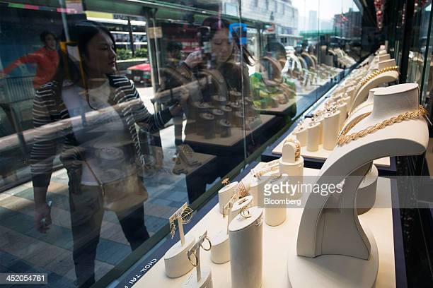 People look at gold jewelry displayed in the window of a Chow Tai Fook Jewellery Group Ltd store in the shopping district of Tsim Sha Tsui in Hong...