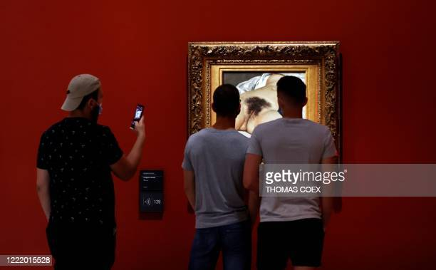 "People look at Gustave Courbet' s painting ""L'origine du monde"" as they visit the Orsay museum on its reopening day, on June 23 in Paris, as France..."